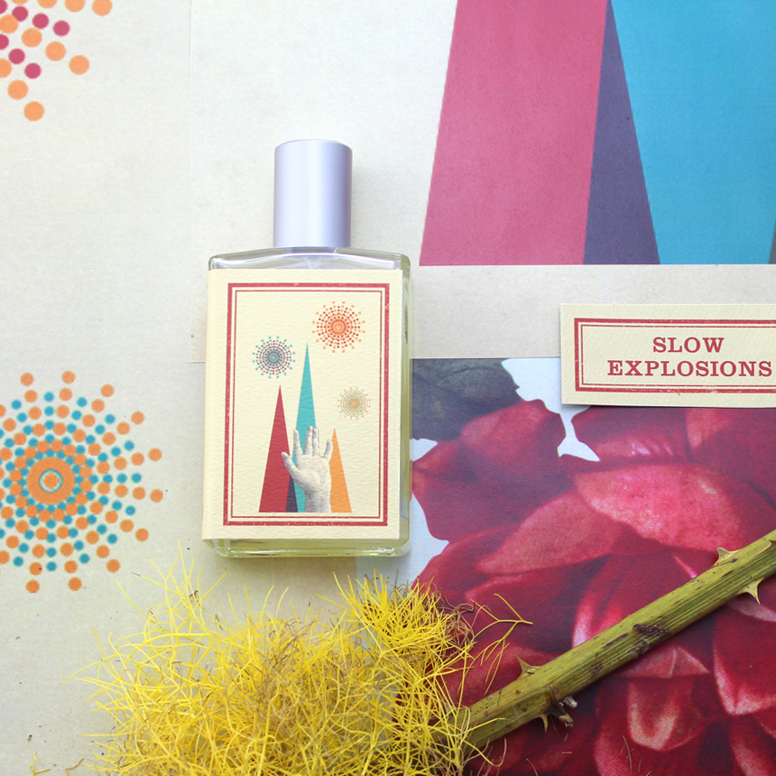 a bottle of Slow Explosions next to a saffron in blossom against a pink, blue, orange and white background